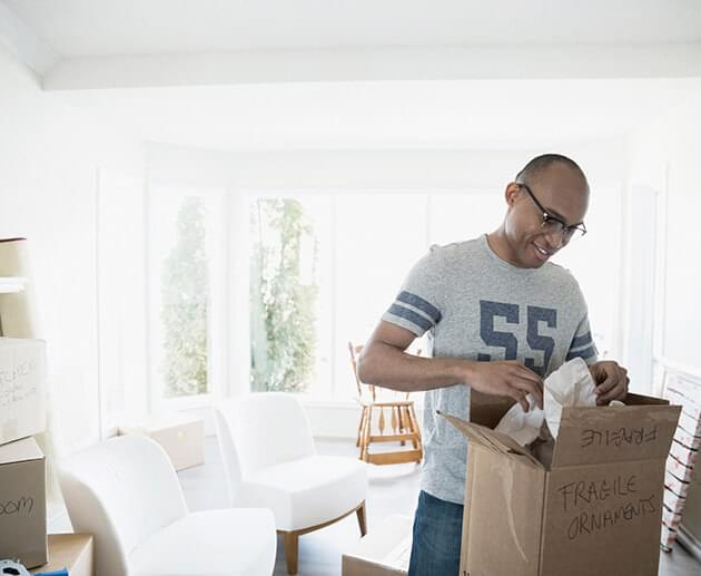 Man packing moving box in living room