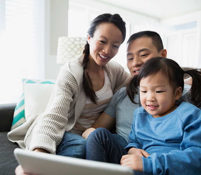 Smiling Asian couple with young daughter looking at laptop