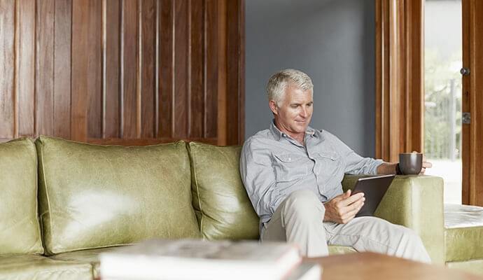 Man using digital tablet while having coffee