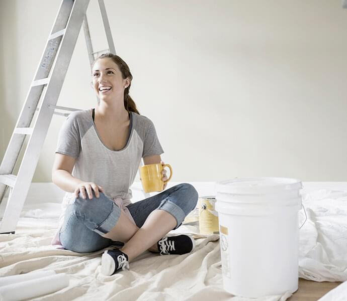 Smiling woman drinking coffee on paint drop cloth