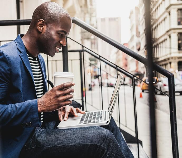 Man sitting on steps with laptop